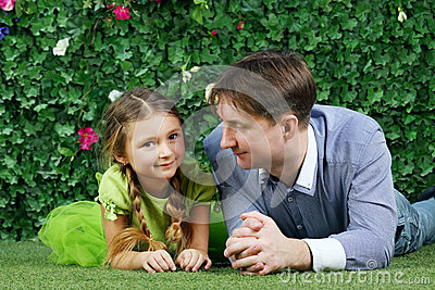 Happy father and little daughter lie on grass