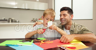 Happy father and son doing arts and crafts at kitchen for Arts and crafts kitchen table