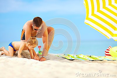 Happy father and son having fun on the beach