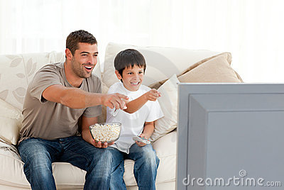 Happy father and son watching television