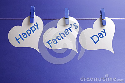 Happy Fathers Day message written on white heart shape tags hanging from blue pegs on a line