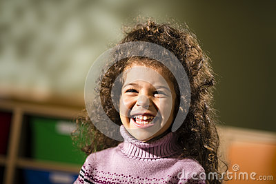 Happy female child smiling for joy in kindergarten