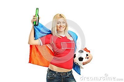 Happy female fan holding a beer bottle and flag