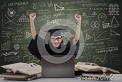 Happy female graduate raise hands in class