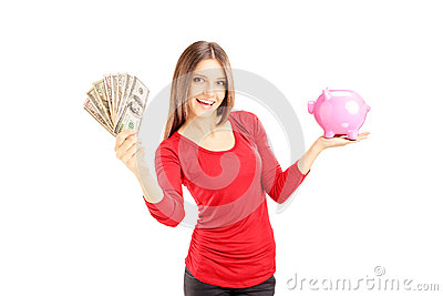 Happy female holding US dollars and pink piggy bank
