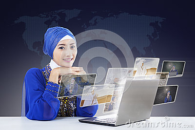 Happy female muslim searching online pictures on laptop