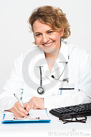 Happy female physician at work desk