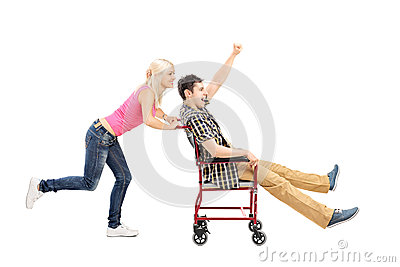Happy female pushing a man in wheelchair