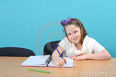 Happy female schoolchild doing her school work