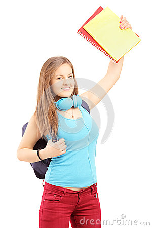 Happy female student with bag holding books and gesturing happin