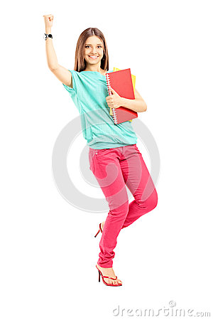 Happy female student holding books and gesturing happiness