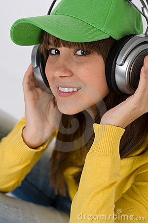 Happy female teenager enjoy music with headphones