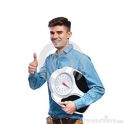 Free Happy Fit Casual Man Holding Scale And Makes Ok Sign Royalty Free Stock Images - 111948509