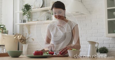 Happy fit young woman cutting vegetable salad in kitchen stock video