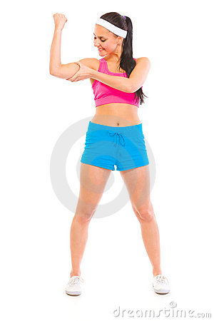 Happy fitness girl checking her muscles
