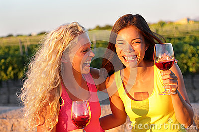 Happy friends drinking wine laughing