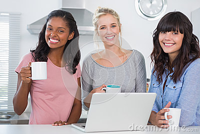 Happy friends having coffee together with laptop