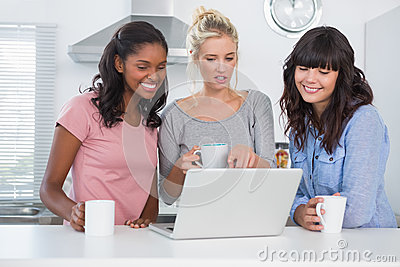 Happy friends having coffee together and looking at laptop