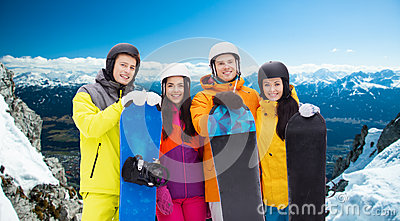 Happy friends in helmets with snowboards outdoors Stock Photo