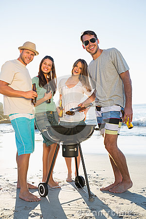 Happy friends looking at camera while having barbecue together
