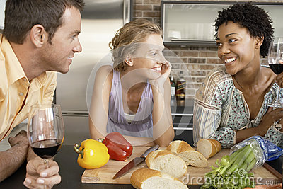Happy Friends With Preparing Food At Kitchen Counter