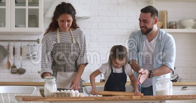 Happy full family having fun, preparing homemade bakery. Overjoyed married couple playing with flour while little preschool daughter learning using rolling pin stock footage