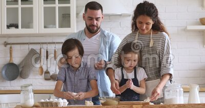 Happy full family kneading dough, having fun together at home. Smiling married couple playing with joyful little kids siblings while making homemade bakery stock video footage