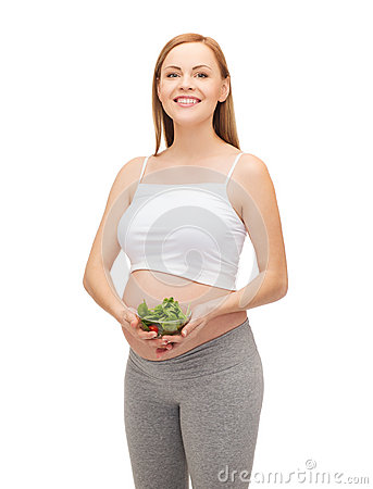 Happy future mother with bowl of salad