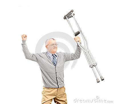 A happy gentleman patient holding crutches and gesturing