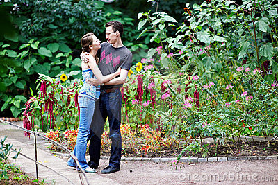 Happy girl in arms of her boyfriend among flowers