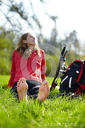 Free Happy Girl Biker Enjoying Relaxation Sitting Barefoot In Green Grass Stock Photography - 30778582