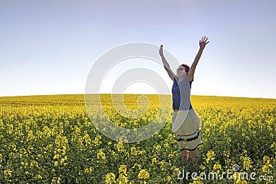 Happy Girl among Canola Plants under Blue Sky