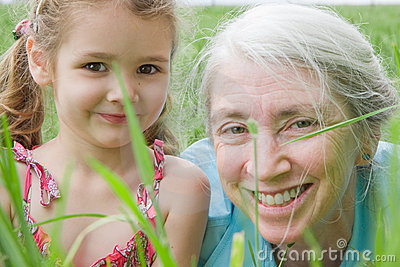 Happy girl child and grandmother in field