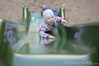 Happy girl  climbing on children s slide