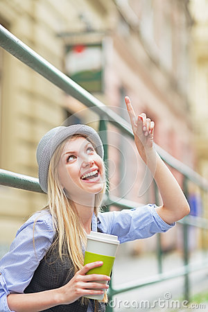 Happy girl with cup of hot beverage pointing on copy space
