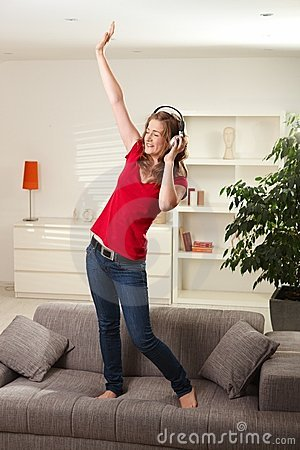 Happy girl dancing on couch with headphones