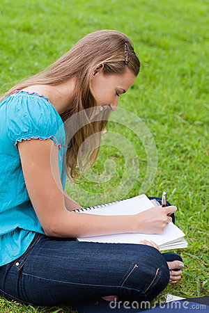 Happy girl doing her homework while sitting down