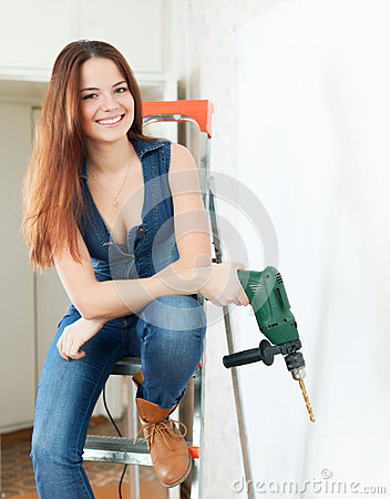 Happy girl with drill on stepladder