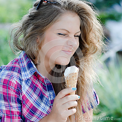 Happy girl eating ice cream outdoors