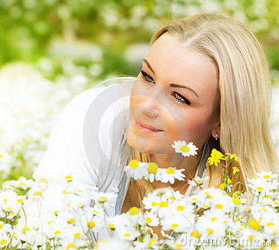 Happy girl enjoying daisy flower field