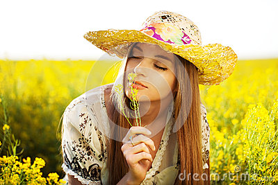 Happy girl enjoys the smell of a flower