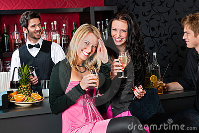 Happy girl friends with drinks enjoying party