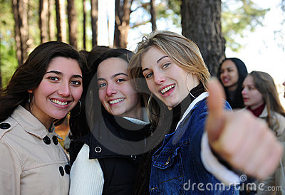 Happy girl with friends showing thumbs up sign