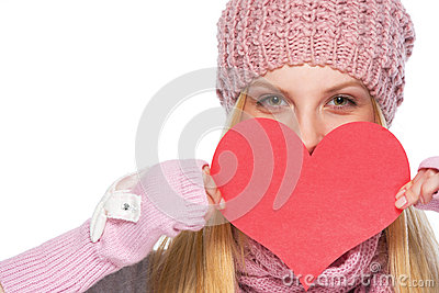 Happy girl hiding behind heart shaped valentines postcard