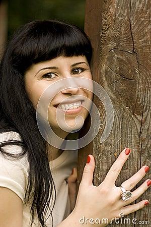 Happy girl hiding behind a tree
