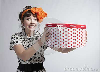 Happy girl holding gift box with red polka dots