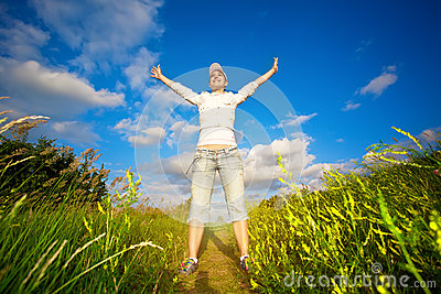 Happy girl is jumping over the blue sky