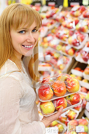 Happy girl keeps packed apples in store