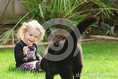 Happy girl laughs as cat walks towards her
