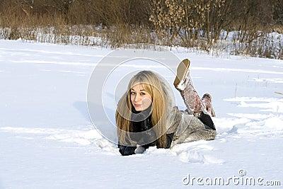 Happy girl lying on snow